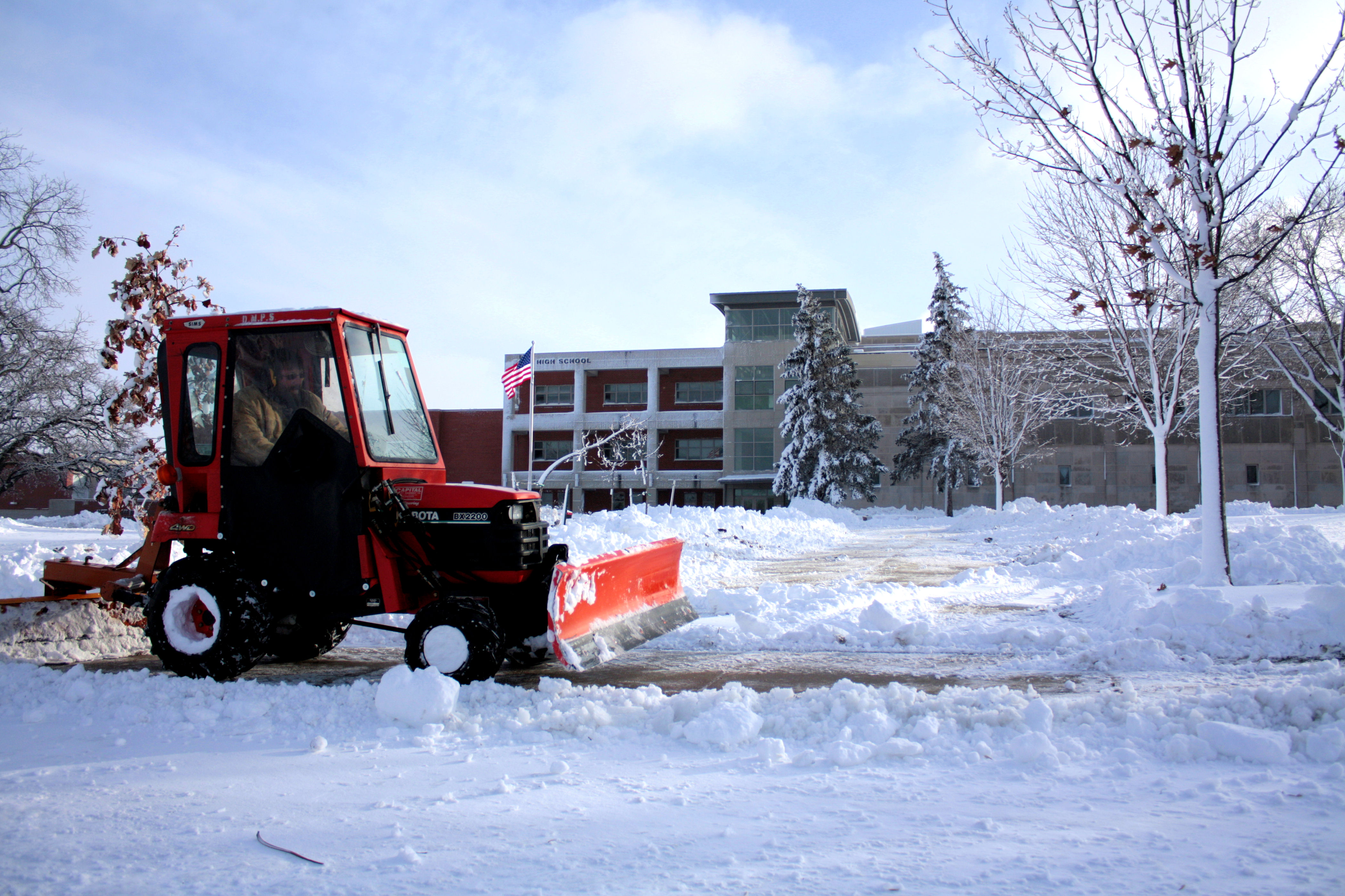 Snow plow clearing sidewalk in front of school